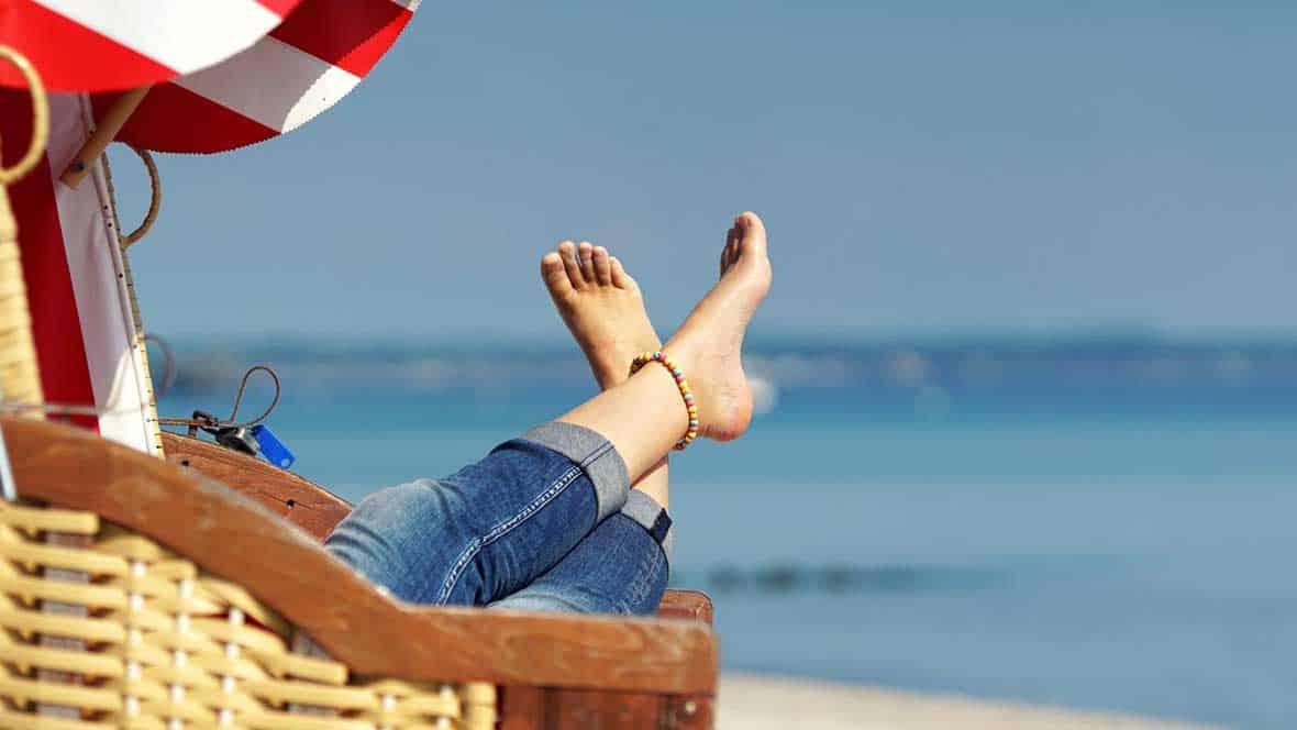 Frau sitzt in einer Liege am Strand