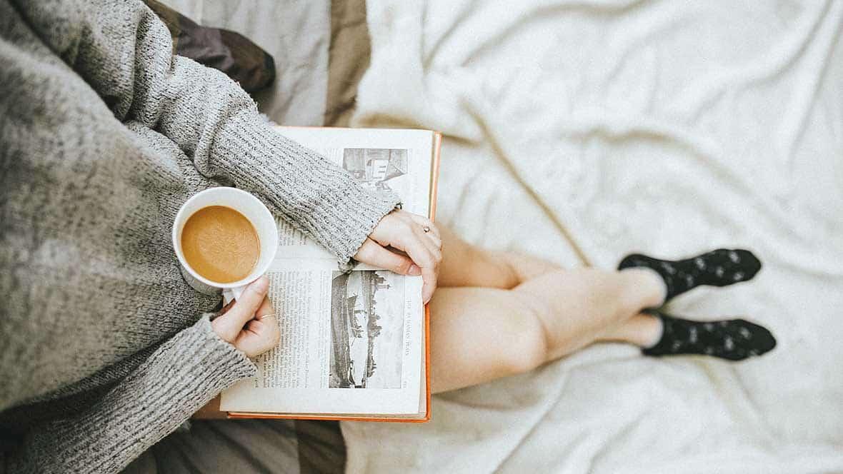 Frau sitzt mit Kaffee und Buch auf dem Schoß