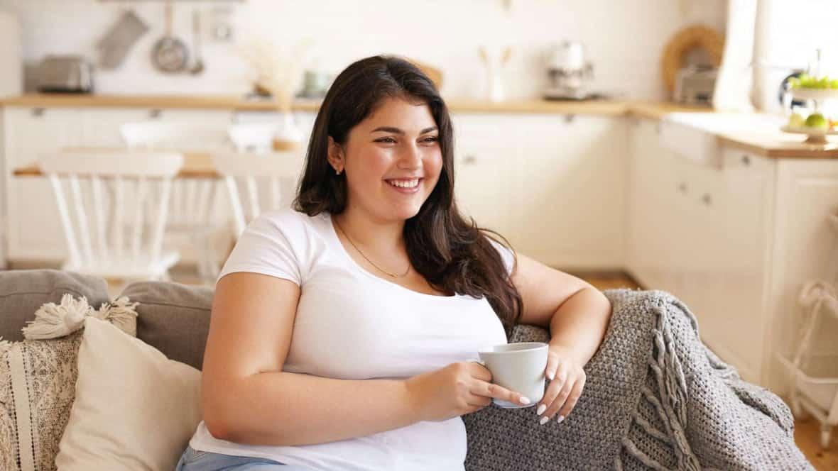 Frau sitzt mit Tasse auf dem Sofa