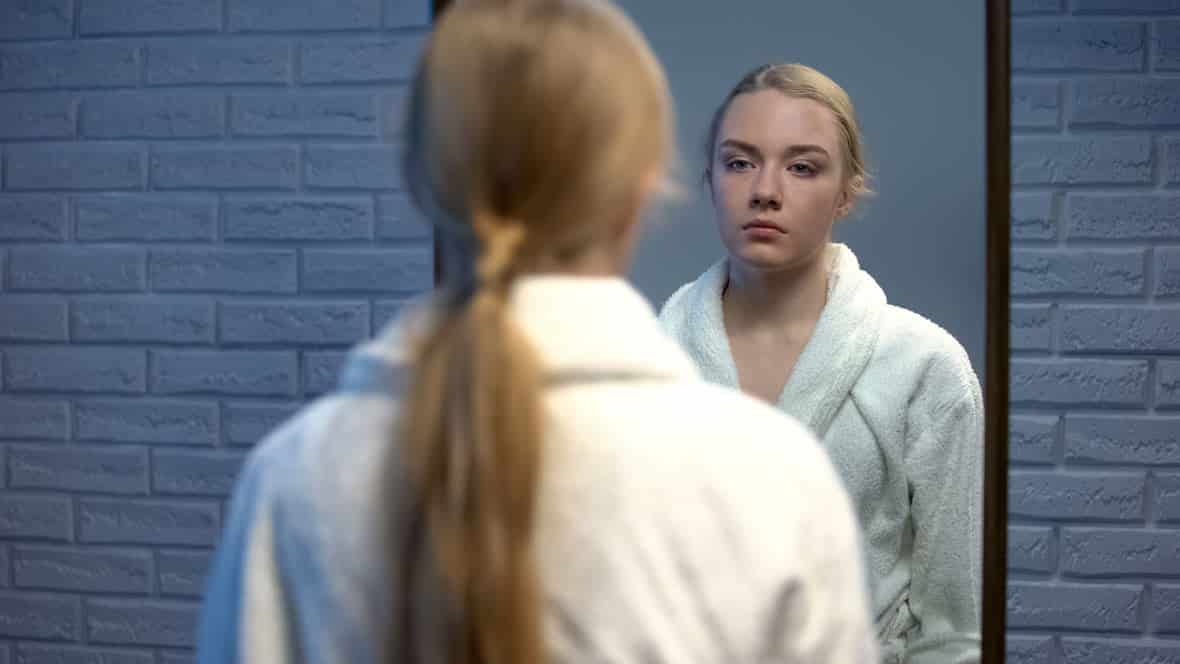 Frau schaut in einen Spiegel